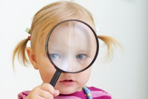 Curious toddler girl looking through magnifier, perfect for early education context